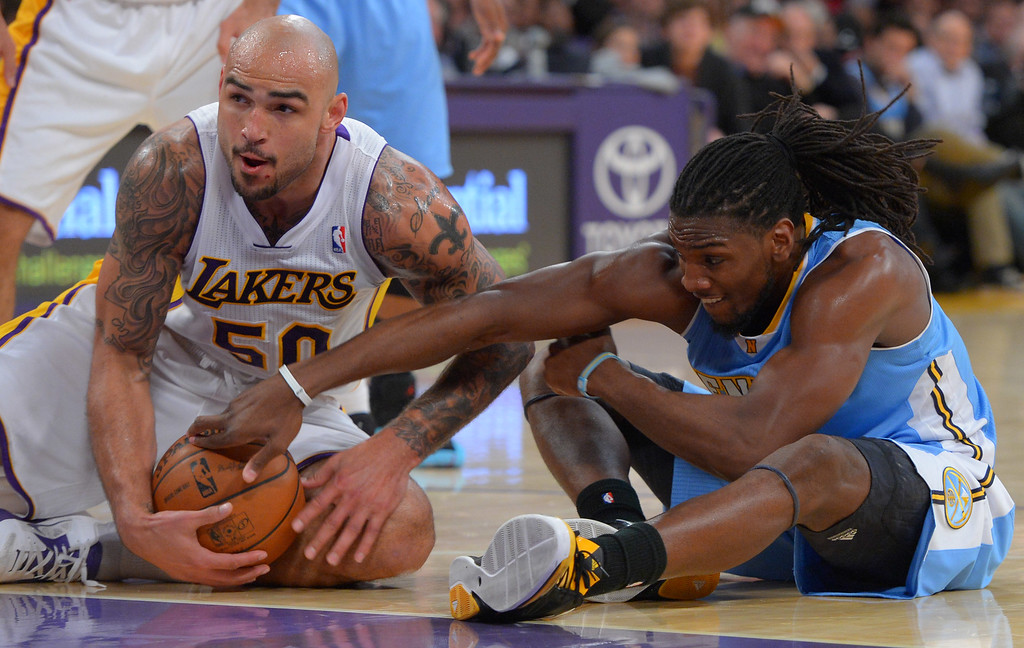 . Lakers Robert Sacre and Nuggets Kenneth Faired scramble for a loose ball at the Staple Center in Los Angeles, CA on Sunday, January 5, 2014. 2nd half. Denver Nuggets beat the Lakers 137-115.  (Photo by Scott Varley, Daily Breeze)