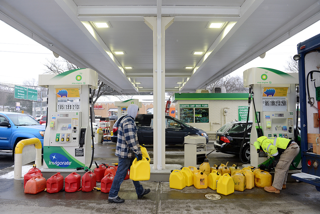 . Dustin Rose, left, and Craig Hueneke, of Xtreme Snow Pros, fill up a total of 27 gas cans in Paramus, N.J., Monday, Jan. 26, 2015. The Philadelphia-to-Boston corridor of more than 35 million people began shutting down as a monster storm, that could unload a paralyzing 1 to 3 feet of snow, moved through the northeast. (AP Photo/Northjersey.com, Tariq Zehawi)