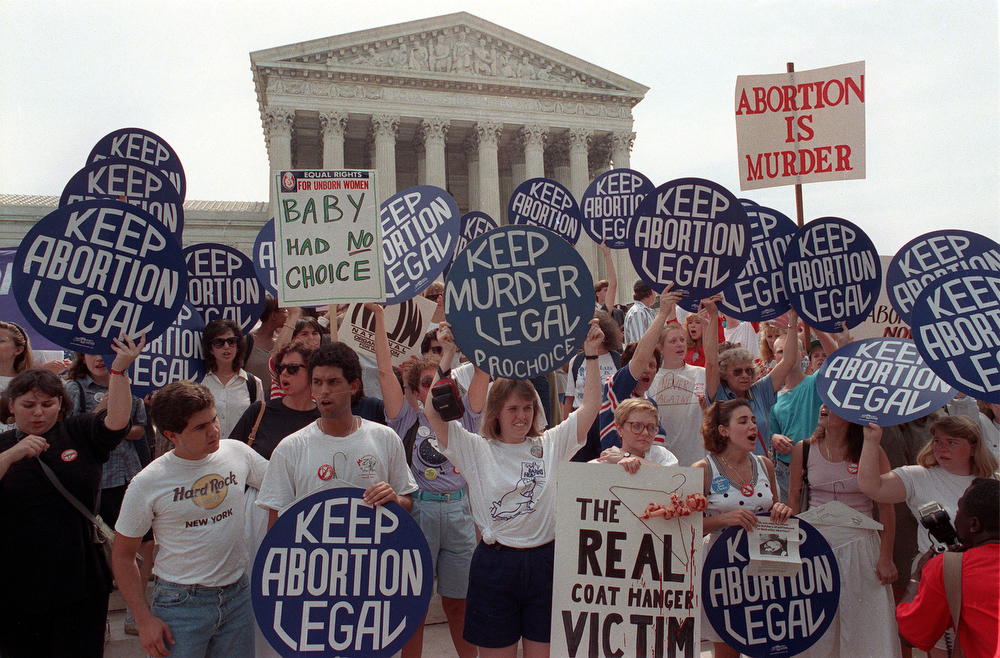 . Pro-life and pro-choice demonstrators hold signs on the steps of the Supreme Court building in Washington, D.C. on July 3, 1989.  The protests came after the court ruled on the Missouri abortion case.  The court\'s decision gave states greater power to limit abortion.  (AP Photo/Ron Edmonds)