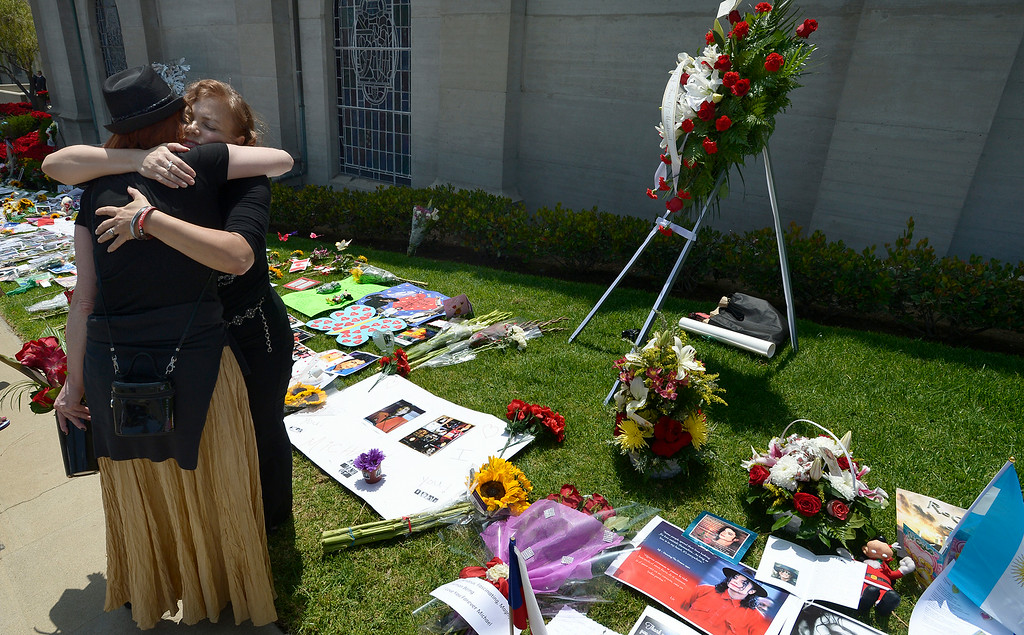 . (l-r) Susan Bryant from Los Angeles, gives a hug to Shirley Alves who traveled from Montreal. Alves arrived with a wreath to honor Michael Jackson. Jackson impersonators, and fans gathered at the Great Mausoleum at Forest Lawn Memorial Park in Glendale to honor Jackson on the 5th anniversary of his death.  Glendale, CA. 6/25/2014 (Photo by John McCoy Daily News)