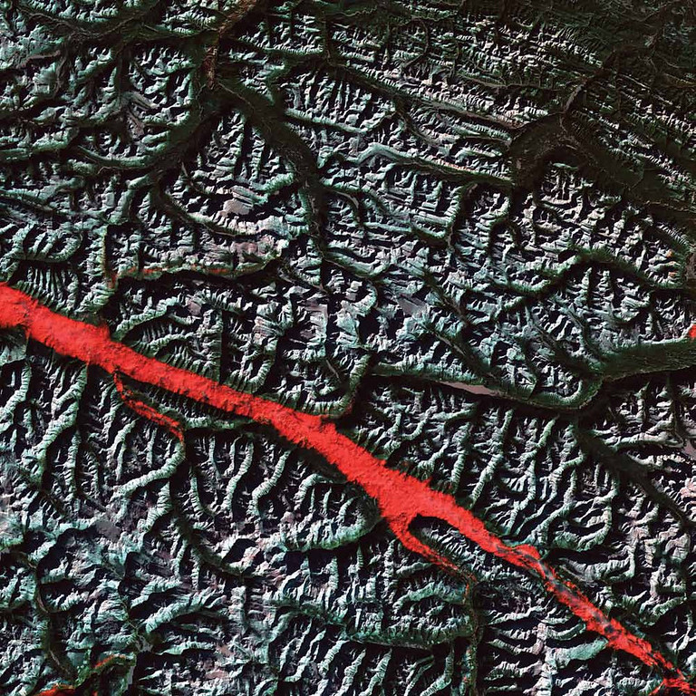 . Rocky Mountain Trench, Canada The stroke of red in this 2004 Landsat 5 image is a remarkable interplay of light and cloud in the Canadian Rockies. The Rocky Mountain Trench is a valley that stretches from the U.S. state of Montana to just south of Canada�s Yukon Territory. It runs parallel with the peaks of the Canadian Rockies, ranging from 3 to 16 kilometers wide. Low clouds filled a part of the Trench near the border between the Canadian provinces of Alberta and British Columbia. The light-reflecting nature of the clouds coupled with low Sun elevation resulted in this startling effect. The Trench aligns with the Fraser River and makes its way past Mount Robson, the highest peak in the Canadian Rockies. Mount Robson is near the center of this image.   NASA