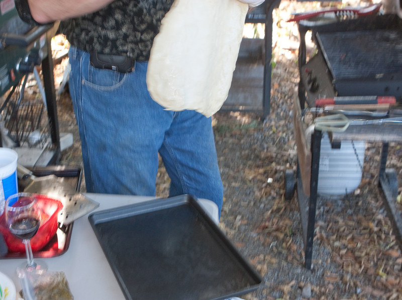 Moving the dough to the nearby BBQ grill.