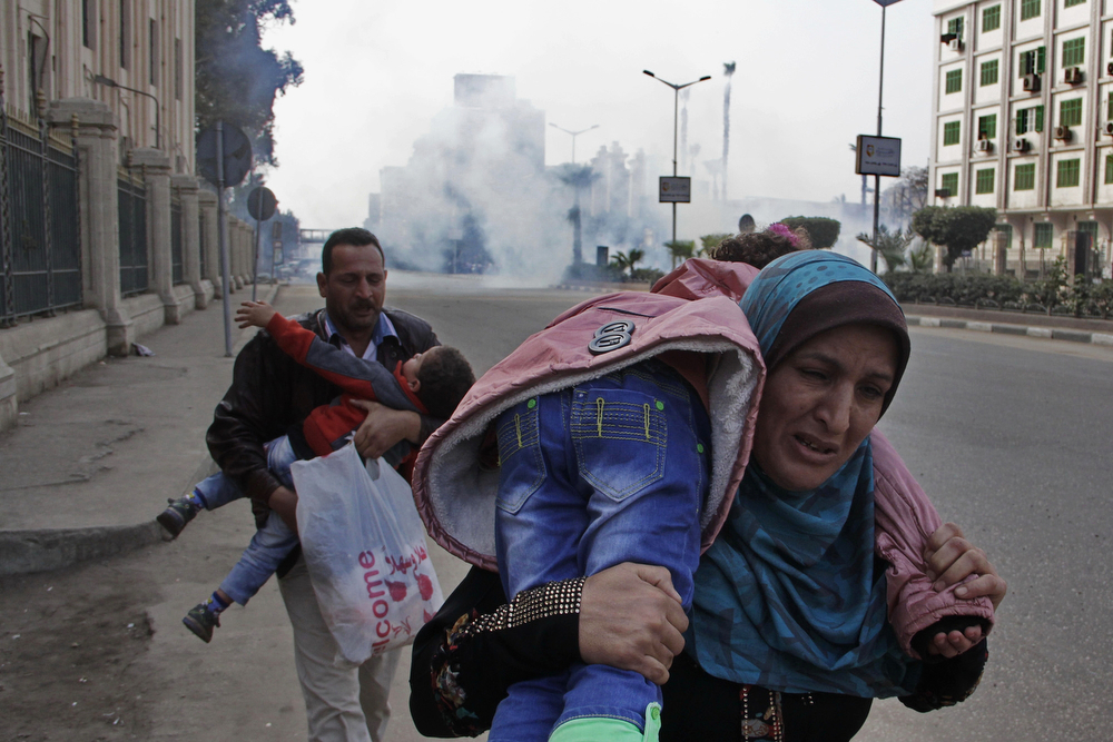 Description of . Family members run away from tear gas during clashes between Egypt's security forces and supporters of ousted President Mohammed Morsi in Cairo, Egypt, Friday, Jan. 17, 2014. Morsi supporters held sporadic protests against this week's constitutional referendum as authorities said there was a deadly clash. (AP Photo/Aly Hazzaa)