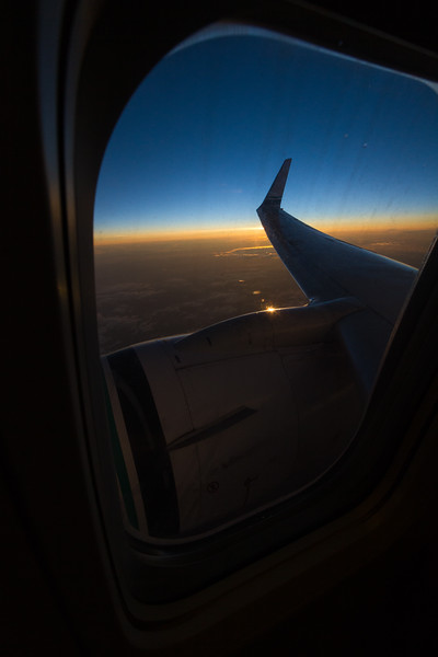 Looking out the airplane window at the engine and wing after sunset with gold and blue