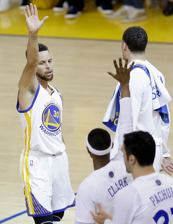 . Golden State Warriors guard Stephen Curry, left, celebrates with teammates during the first half of Game 5 of basketball\'s NBA Finals against the Cleveland Cavaliers in Oakland, Calif., Monday, June 12, 2017. (AP Photo/Marcio Jose Sanchez)