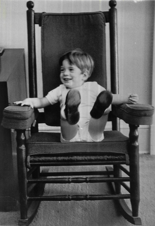 . Three-year-old John F. Kennedy, Jr., kicks back and forth in a rocking chair, something his father was instrumental in re-popularizing, in the White House office of the president\'s secretary, Mrs. Evelyn Lincoln, in 1963.  Denver Post file
