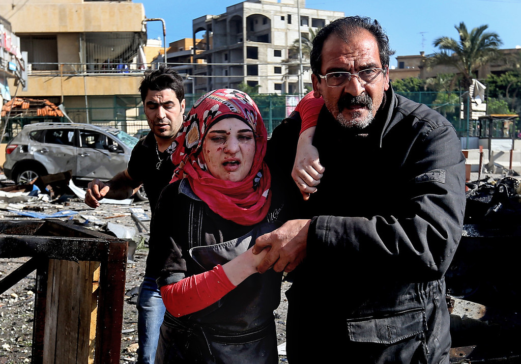 . A Lebanese man helps an injured woman, as they pass the site of an explosion, near the Kuwaiti Embassy and Iran\'s cultural center, in the suburb of Beir Hassan, Beirut, Lebanon, Wednesday, Feb. 19, 2014.  (AP Photo/Hussein Malla)