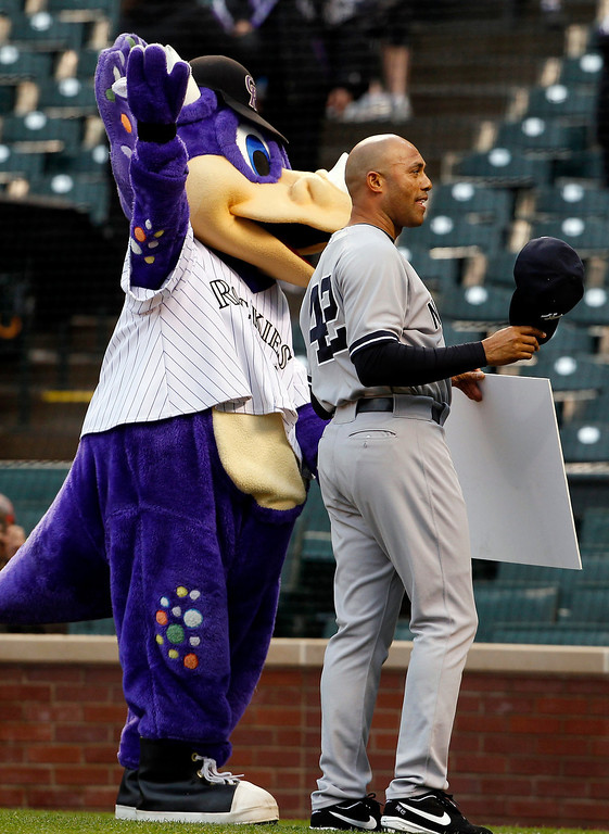 . New York Yankees relief pitcher Mariano Rivera, right, accepts a check for his foundation from Colorado Rockies mascot Dinger the dinosaur during a ceremony to honor Rivera before the first inning of a baseball game in Denver on Wednesday, May 8, 2013. (AP Photo/David Zalubowski)