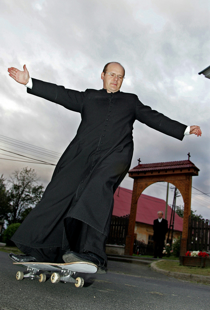 . Reverend Zoltan Lendvai, a Hungarian Roman Catholic Church priest, 45, rides his skateboard in front of the local catholic church, a small village nearby the Hungarian-Slovenian border on August 18, 2010. Zoltan Lendvai lives here and preaches in other eleven villages in this region, and teaches his young believers to skateboard. Zoltan Lendvai follows the Saint John Bosco, an Italian 19th century priest who teached by using games.  AFP PHOTO / ATTILA KISBENEDEK