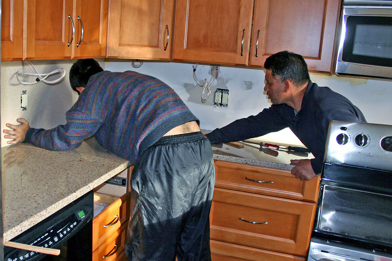 Working to slide the counter top out from under the remaining backsplash!