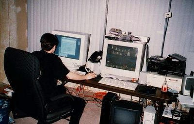 "This picture was taken near the end of Quake 1's development period in 1996.  American is sitting at his desk, checking out my map E2M1 (with the original Quake interface for the Base theme, in fact).  The computer he's using is a NEXTSTEP system made by HP (nicknamed the Gecko), in fact the machine name of his computer was ""idtokay"".  Under his desk, the black hardware looks to be an older NeXT Computer.  The room we were working in at that time was called the War Room -- we were all working in the same room while the rest of the office was being built out.  To the right of American's desk was Tim Willits', and then my desk."