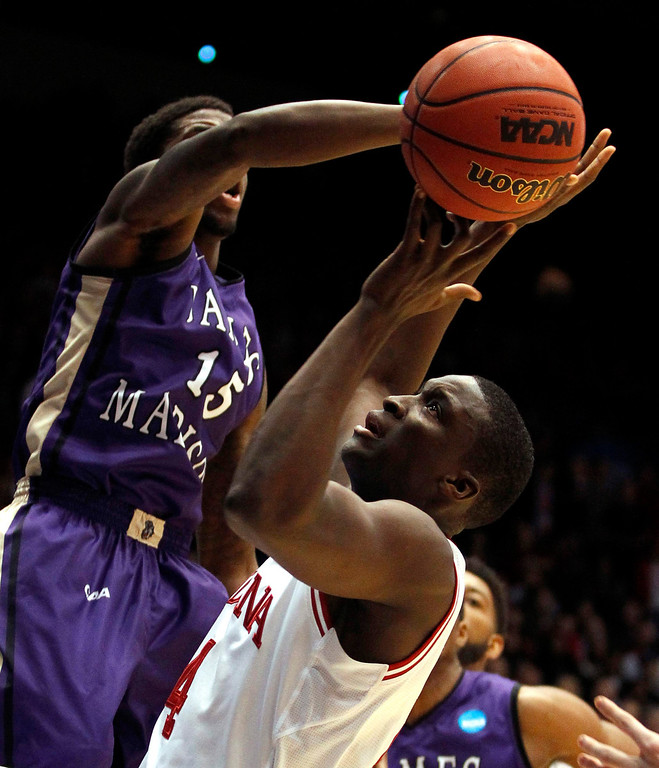 . Indiana Hoosiers guard Victor Oladipo (4) fights for a rebound with James Madison Dukes guard Andre Nation (15) during the first half of their second round NCAA tournament basketball game in Dayton, Ohio March 22, 2013. REUTERS/Matt Sullivan