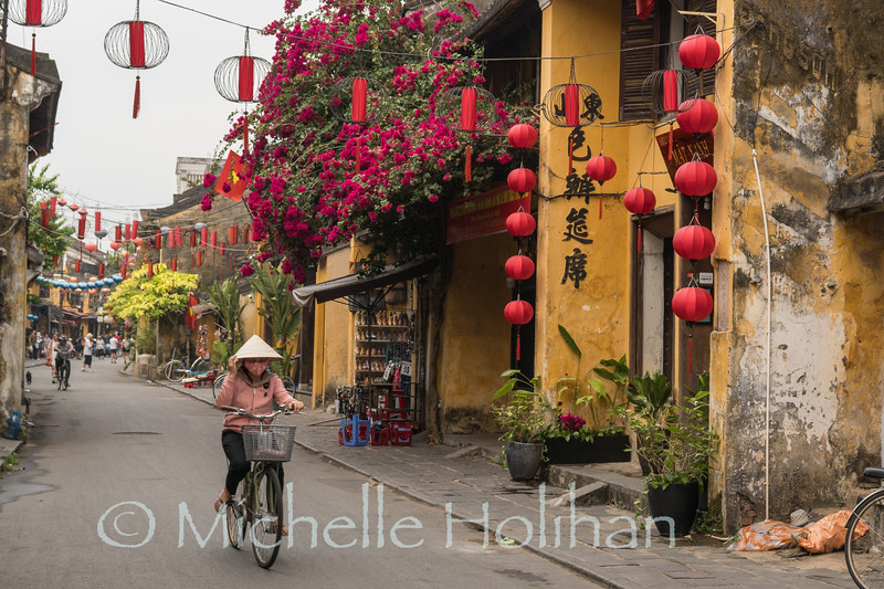 HOI AN, VIETNAM - MARCH 6, 2019: Unidentified woman peddles her bike down the street in the Old City.