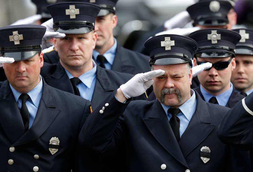 Description of . Firefighters salute as the funeral procession of Boston Fire Lt. Edward Walsh arrives outside the Church of Saint Patrick in Watertown, Mass., Wednesday, April 2, 2014. Walsh and Boston Firefighter Michael Kennedy died after being trapped while battling a fire in Boston. (AP Photo/Charles Krupa)