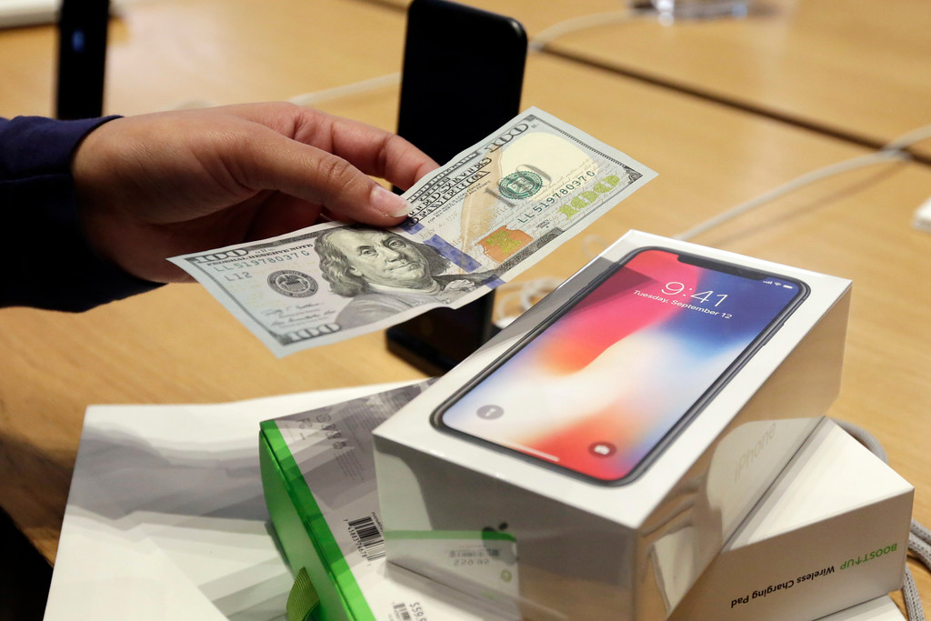 . A customer hands over cash as she pays for an iPhone X at the Apple Store on New York\'s Fifth Avenue, Friday, Nov. 3, 2017. (AP Photo/Richard Drew)