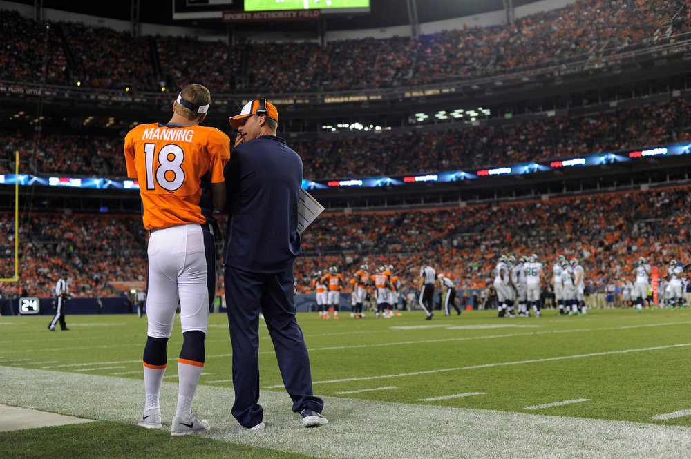 . Denver Broncos offensive coordinator Adam Gase talks with Denver Broncos quarterback Peyton Manning (18) during the second quarter against the Seattle Seahawks August 7, 2014 at Sports Authority Field at Mile High Stadium.  (Photo by John Leyba/The Denver Post)