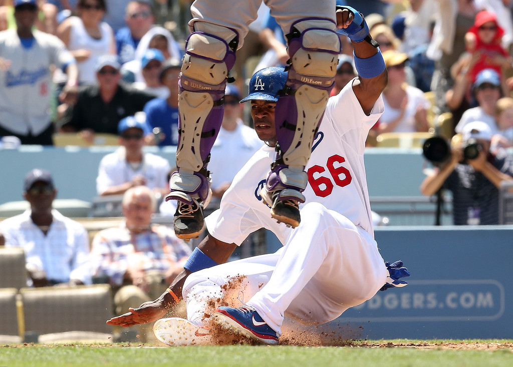 . Yasiel Puig #66 of the Los Angeles Dodgers slides in to home to score a run as catcher Wilin Rosario #13 of the Colorado Rockies leaps for a high throw in the fifth ininng at Dodger Stadium on July 14, 2013 in Los Angeles, California.  (Photo by Stephen Dunn/Getty Images)