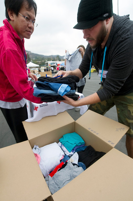 . Lun Sukarna, left of Rosemead and Garnet Tipton of South Pasadena ffolding clothes and putting the clothes in a box to be shipped to Philippine Typhoon Relief Donation Drive. PCC along with Vice Mayor Jacque Robinson, the American Red Cross, Filipino American Television, Victory Cargo, and the PNB-Remittance Centers  sponsoring a Philippine Typhoon Relief Donation Drive Donation Drive Drop-Off Rally Wednesday, November 20, 2013 at the Rose Bowl. (Photo by Walt Mancini/Pasadena Star-News)