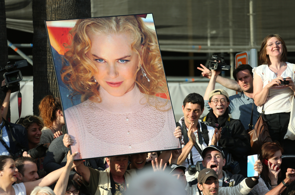 . Fans hold up a giant poster of actress Nicole Kidman as they await arrivals  for the opening ceremony and the screening of Grace of Monaco at the 67th international film festival, Cannes, southern France, Wednesday, May 14, 2014. (Photo by Joel Ryan/Invision/AP)