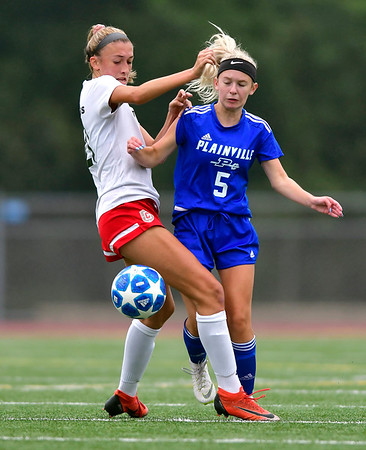 9/12/2019 Mike Orazzi | StaffrConard High School's Madison Lopol (21) and Plainville's Skyler Ibitz (5) on Thursday.
