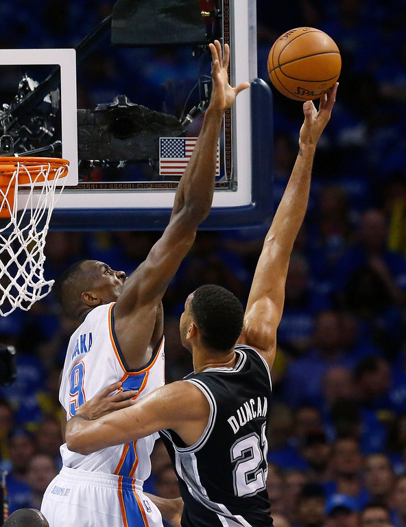 . Oklahoma City Thunder forward Serge Ibaka (9) gets up to block a shot by San Antonio Spurs forward Tim Duncan (21) in the first quarter of Game 3 of an NBA basketball playoff series of the Western Conference finals, Sunday, May 25, 2014, in Oklahoma City. (AP Photo/Sue Ogrocki)
