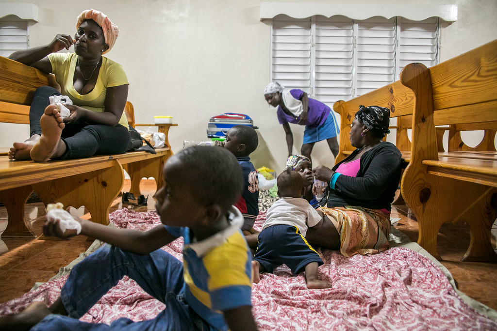 . Families gather at a shelter in a local church during the evening before the arrival of Hurricane Irma in Las Terrenas, Dominican Republic, Wednesday, Sept. 6, 2017. Dominicans wait for the arrival of Hurricane Irma after it lashed Puerto Rico with heavy rain and powerful winds, leaving nearly 900,000 people without power as authorities struggled to get aid to small Caribbean islands already devastated by the historic storm. (AP Photo/Tatiana Fernandez)
