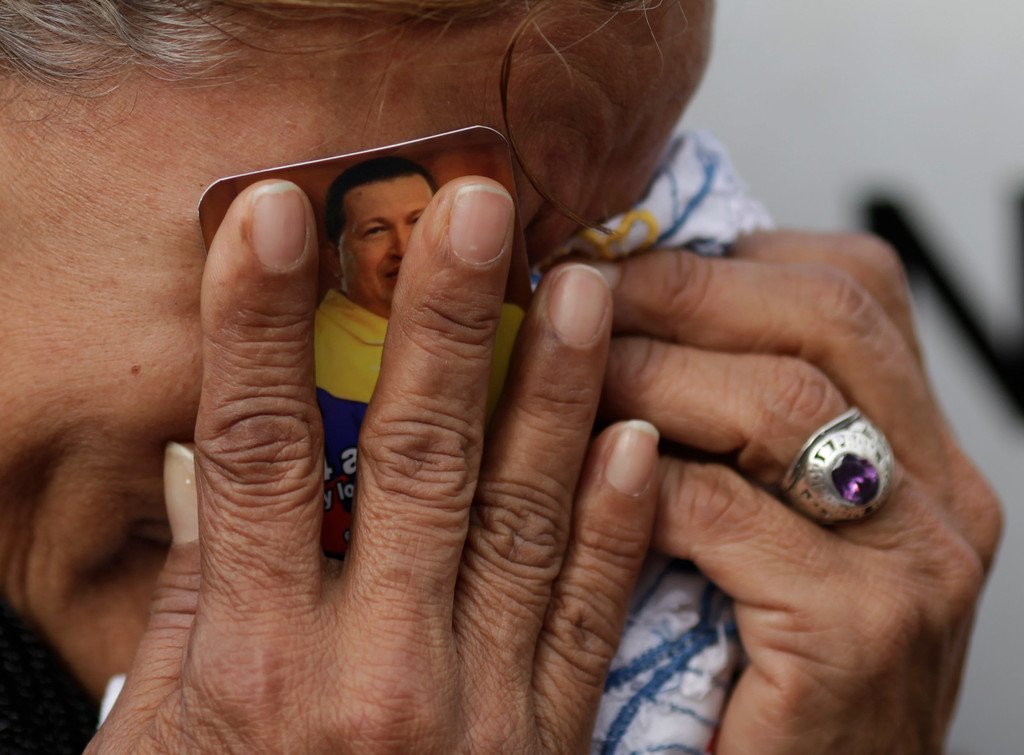 . A woman holds a picture of President Hugo Chavez against her face as she cries outside the military hospital where he died Tuesday in Caracas, Venezuela, Wednesday, March 6, 2013.(AP Photo/Ariana Cubillos)