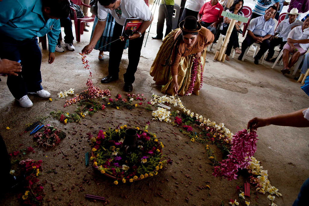 """. Peru\'s Congresswoman, Quechua Indian Claudia Coari, center, puts flowers on an altar named \""""Offering to the earth\"""" during visit the indigenous neighborhood of Monimbo in Masaya, Nicaragua, Wednesday, April 10, 2013.  Coari is in Nicaragua, along with legislators from Nicaragua, Peru, Bolivia, Chile, Colombia, Ecuador, Guatemala, Honduras, Mexico, Panama and Venezuela, for the 13th ordinary session of the Indigenous Parliament of America. (AP Photo/Esteban Felix)"""