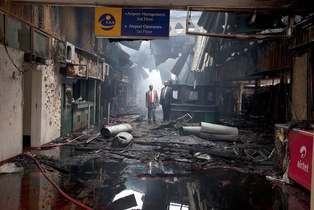 . Kenyan airport officials view the damage after a fire engulfed the international arrivals area of Jomo Kenyatta International Airport, in Nairobi, Kenya, on Wednesday, Aug. 7, 2013.   (AP Photo/Sayyid Azim)