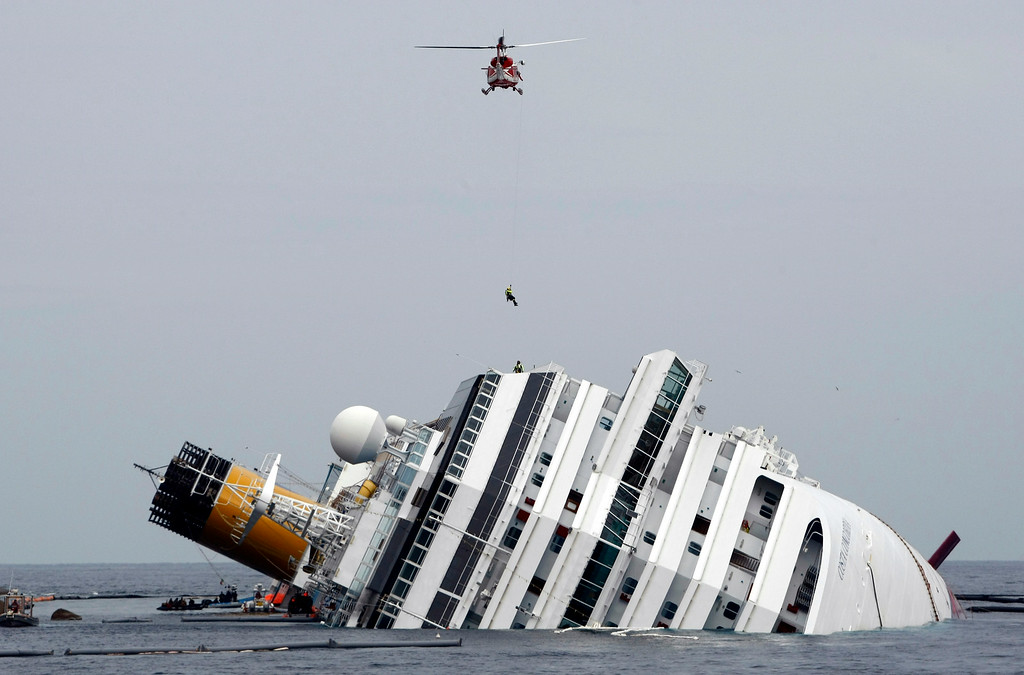 . This Jan. 31, 2012 file photo shows an Italian firefighter being lowered from a helicopter onto the grounded cruise ship Costa Concordia off the Tuscan island of Giglio, Italy. Court-appointed experts have pointed the finger of blame primarily at the captain of a cruise ship that ran aground off Italy, but also faulted the crew and ship owner for a series of blunders, delays and security breaches that contributed to the disaster and the deaths of 32 people. (AP Photo/Pier Paolo Cito, file)
