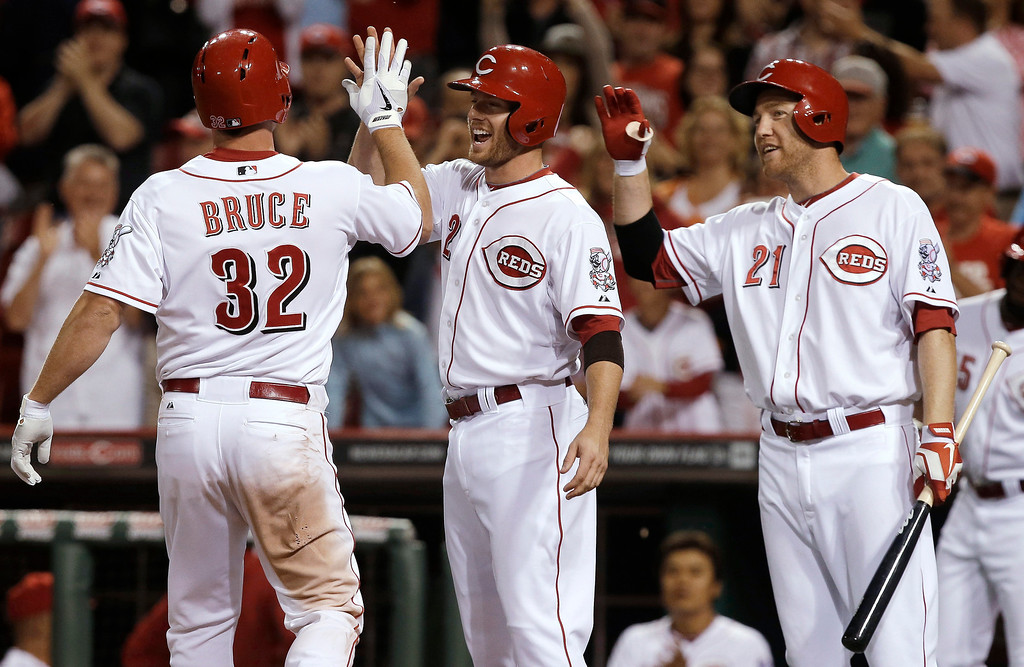 . Cincinnati Reds\' Jay Bruce (32) is met at home by Zack Cozart (2) and Todd Frazier (21) after Bruce hit a two-run home run off Colorado Rockies relief pitcher Josh Outman in the eighth inning of a baseball game, Monday, June 3, 2013, in Cincinnati. Cincinnati won 3-0. (AP Photo/Al Behrman)
