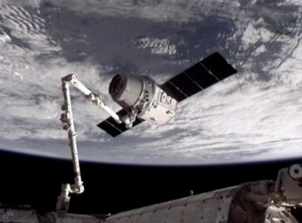 . This image provided by NASA-TV shows the SpaceX Dragon commercial cargo craft, top, after Dragon was grappled by the Canadarm2 robotic arm and connected to the International Space Station, Friday, May 25, 2012. Dragon is scheduled to spend about a week docked with the station before returning to Earth on May 31 for retrieval. (AP Photo/NASA)