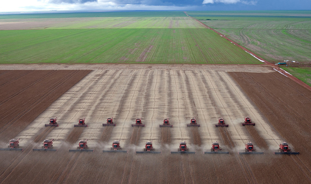. Workers use combines to harvest soybeans in Tangara da Serra, State of Mato Grosso, Brazil, Tuesday, March 27, 2012.  Brazil is the world\'s second largest soy producer after the United States and the crop is one of the nation\'s principal exports. (AP Photo/Andre Penner)
