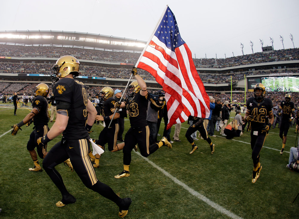 . Army\'s Dan McGue runs the flag onto the field with an American flag before an NCAA college football game against Navy, Saturday, Dec. 8, 2012, in Philadelphia. (AP Photo/Matt Slocum)