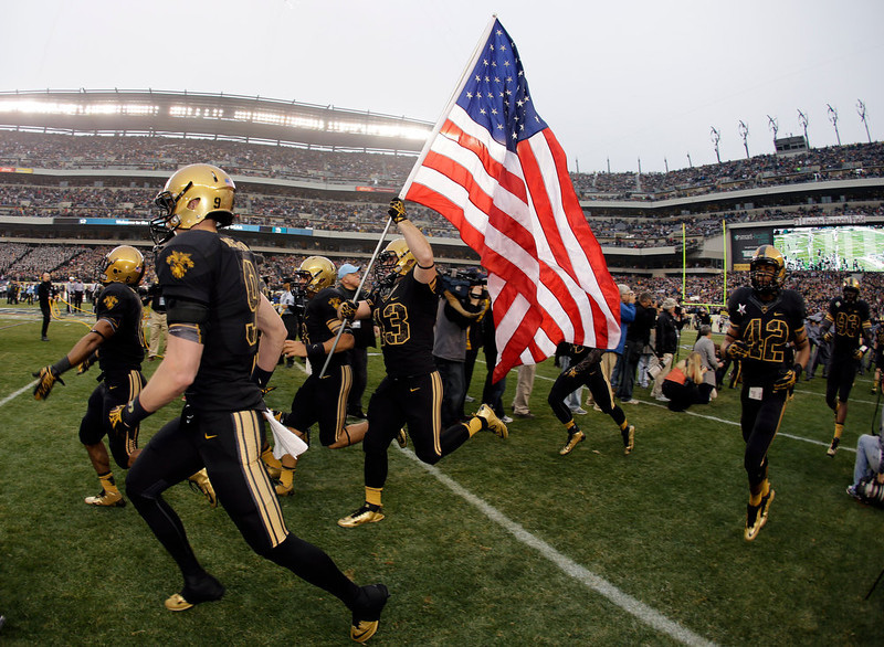 . Army\'s Dan McGue runs the flag onto the field with an American flag before an NCAA college football game against Navy, Saturday, Dec. 8, 2012, in Philadelphia. (AP Photo/Matt Slocum)