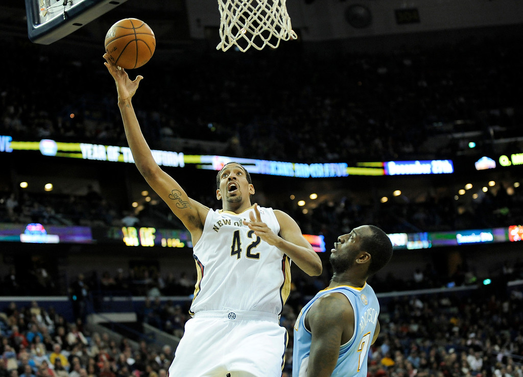 . New Orleans Pelicans center Alexis Ajinca (42) shoots over Denver Nuggets forward J.J. Hickson (7) in the second half of an NBA basketball game in New Orleans, Friday, Dec. 27, 2013. New Orleans won 105-89. (AP Photo/Stacy Revere)