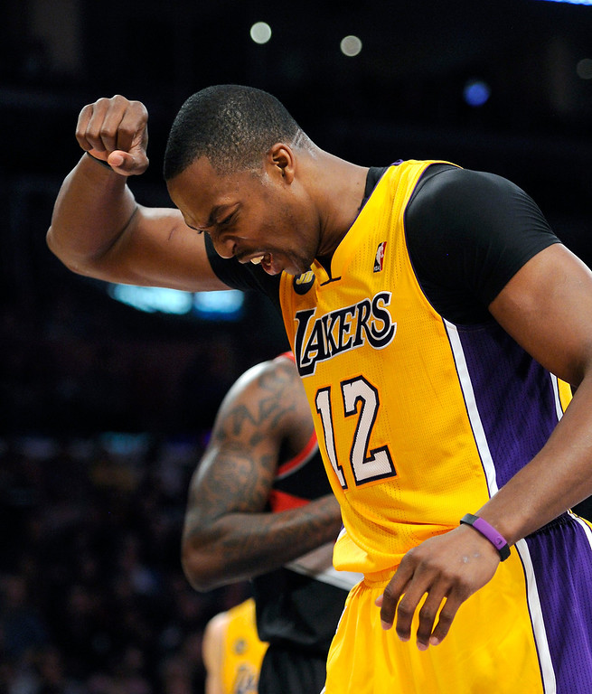 . The Lakers\' Dwight Howard grimaces after being fouled on his injured shoulder by the Trail Blazers in the first half, Friday, February 22, 2013, at Staples Center. (Michael Owen Baker/L.A. Daily News)