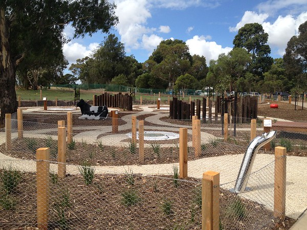 water fountain and cow sculpture and concrete path maze with timber poles