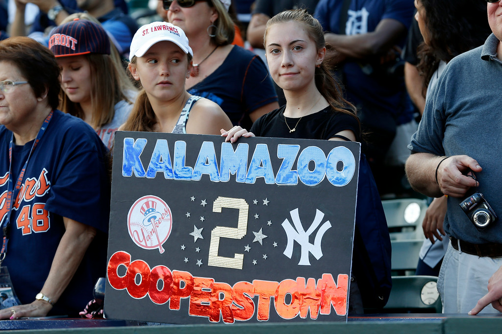 . Fans hold a sign to honor New York Yankees shortstop and Michigan native Derek Jeter during a special pre-game on-field ceremony before a baseball game against the Detroit Tigers in Detroit Wednesday, Aug. 27, 2014. (AP Photo/Paul Sancya)