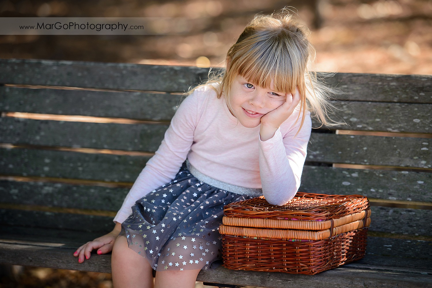 little girl in navy blue skirt with golden stars sitting on the bench at Mountain View Shoreline Lake Park