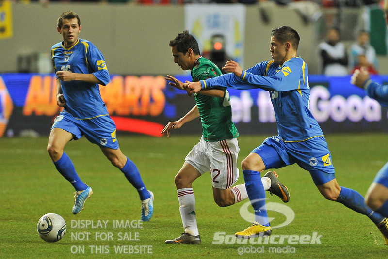 Mexico's Defender Paul Aguilar (#22) attempts to get away from the defense in Soccer action between Bosnia-Herzegovina and Mexico.  Mexico defeated Bosnia-Herzegovina 2-0 in the game at the Georgia Dome in Atlanta, GA.