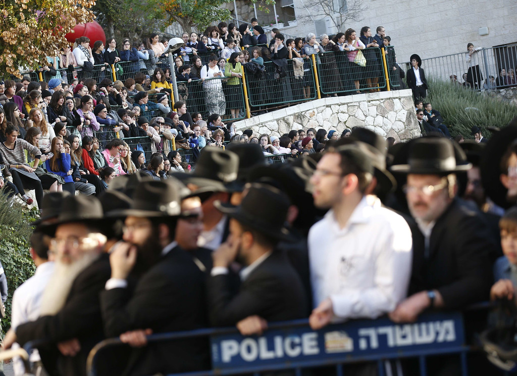 . Ultra-orthodox Jews watch emergency personnel clean up and secure the area of an attack, by two Palestinians, on Israeli worshippers at a synagogue in the ultra-Orthodox Har Nof neighborhood in Jerusalem on November 18, 2014. AFP PHOTO/ JACK GUEZ/AFP/Getty Images
