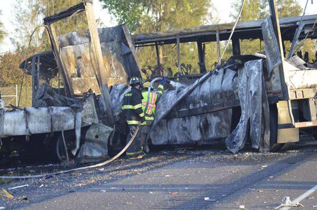 . Firefighters hose down the wreckage of a bus and a semitruck that collided, Thursday, April 10, 2014, just north of Orland, Calif., that left at least nine dead. Authorities said it is not yet clear what caused the crash but that it involved a tour bus, a FedEx truck and a Nissan Altima. (AP Photo/The Chico Enterprise-Record, Dan Reidel)