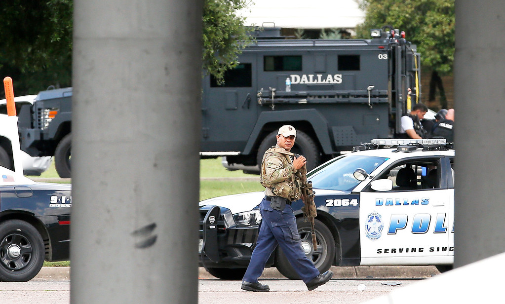 . A sniper walks by the intersection of Dowdy Ferry Rd and Interstate 45 during a stand off with a gunman barricaded inside a van near by, Saturday, June 13, 2015, in Hutchins, Texas. The gunman allegedly attacked Dallas Police Headquarters. (AP Photo/Brandon Wade)