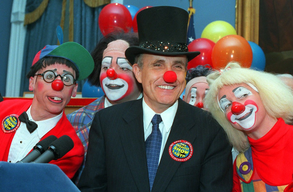 . New York City Mayor Rudolph W. Giuliani, center, doffed with a red clown nose and ringmaster\'s top hat, is joined by Ringling Brothers Barnum and Bailey Circus clowns Chris Allison, left, and Karen DeSanto, right, at City Hall Tuesday, Feb. 23, 1999, in New York.  (AP Photo/Marty Lederhandler)