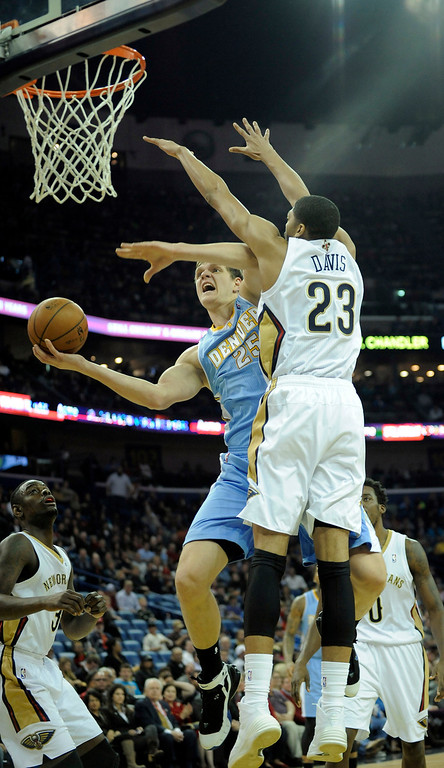 . Denver Nuggets center Timofey Mozgov (25) shoots under New Orleans Pelicans center Anthony Davis (23) during the first half of an NBA basketball game in New Orleans, Friday, Dec. 27, 2013. (AP Photo/ Stacy Revere)