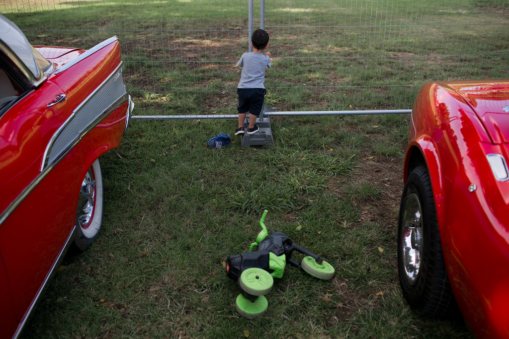 ". A boy looks through a fence during the 31st annual ""Five Club\"" car collectors\' meeting in Ramat Gan, Israel, Friday, Oct. 6, 2017. Each weekend, at Israeli gas stations and parking lots and parks, car collectors gather with their beauties _ and take a step back in time. (AP Photo/Oded Balilty)"