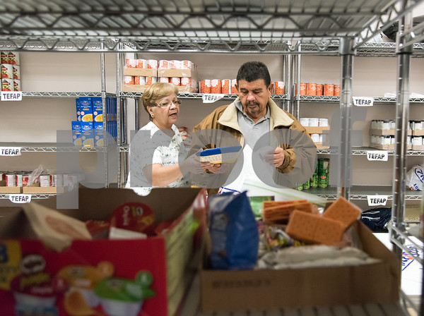 11/21/17 Wesley Bunnell | Staff The New Britain Salvation Army has seen a 100 percent increase in families looking for assistance from the food pantry since August in part due to the hurricanes. Food pantry volunteers Mirta Soto, L, and Harry Cabaralo go through the list of requirements for a customer.