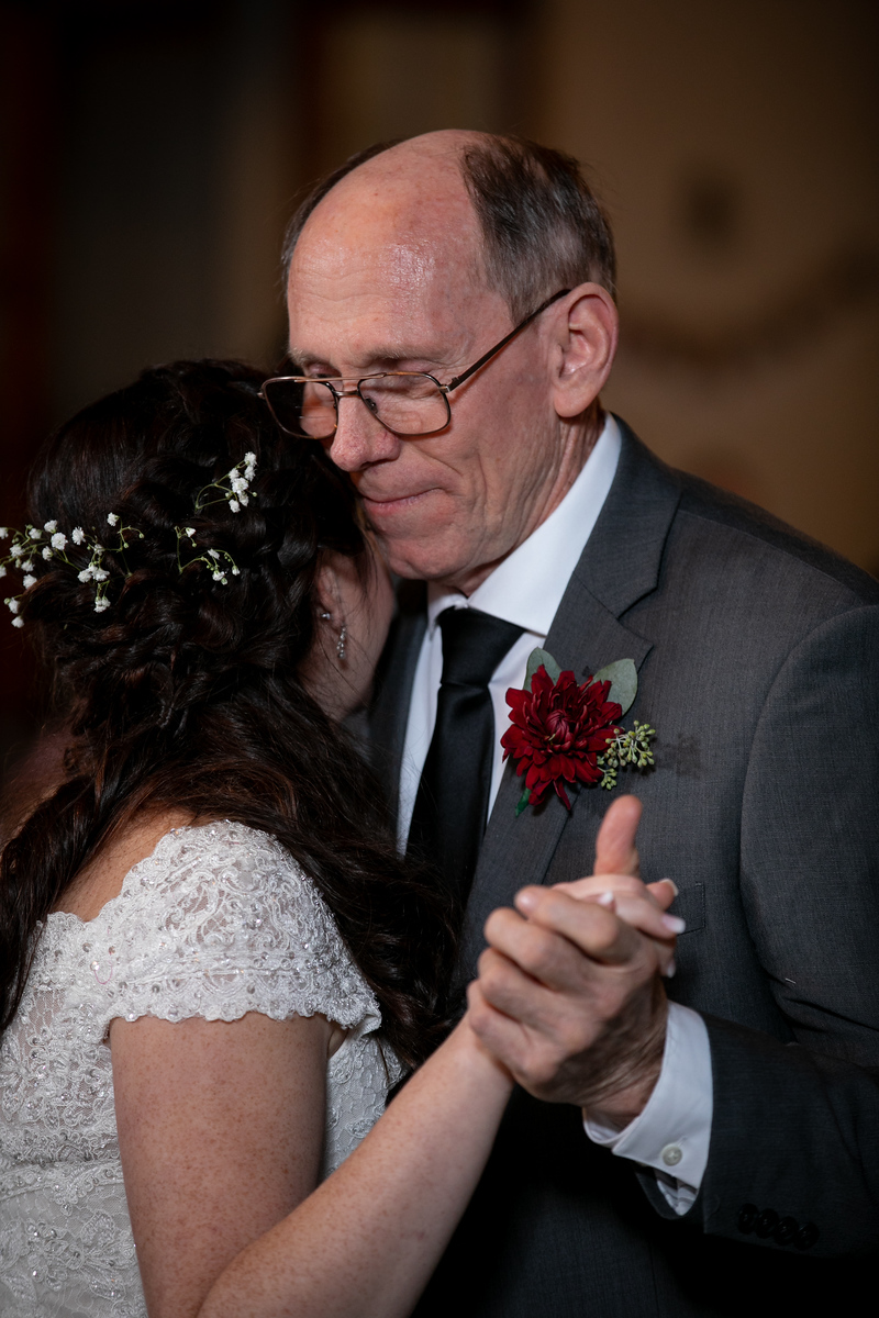 father wearing a grey suit with a crimson boutonniere dancing with his daughter on her wedding night