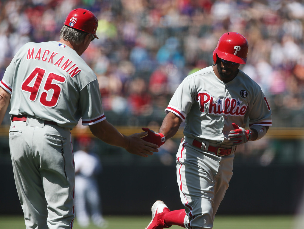 . Philadelphia Phillies third base coach Pete Mackanin, left, congratulates Jimmy Rollins who circles the bases after hitting a solo home run against the Colorado Rockies in the first inning of a baseball game in Denver, Sunday, April 20, 2014. (AP Photo/David Zalubowski)